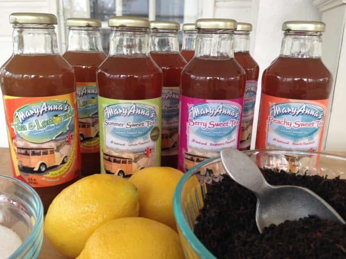 Artisan Brewed Iced Tea in bottles with loose tea and lemons start a food business