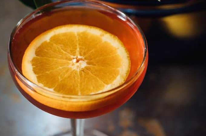 Enchanting Earl Grey tea cocktail made with Grand Marnier and garnished with an orange slice