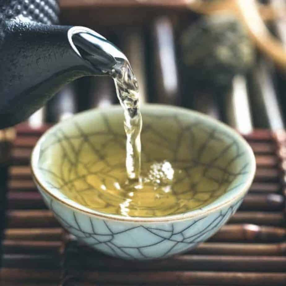 pouring green tea into cup for drinking tea