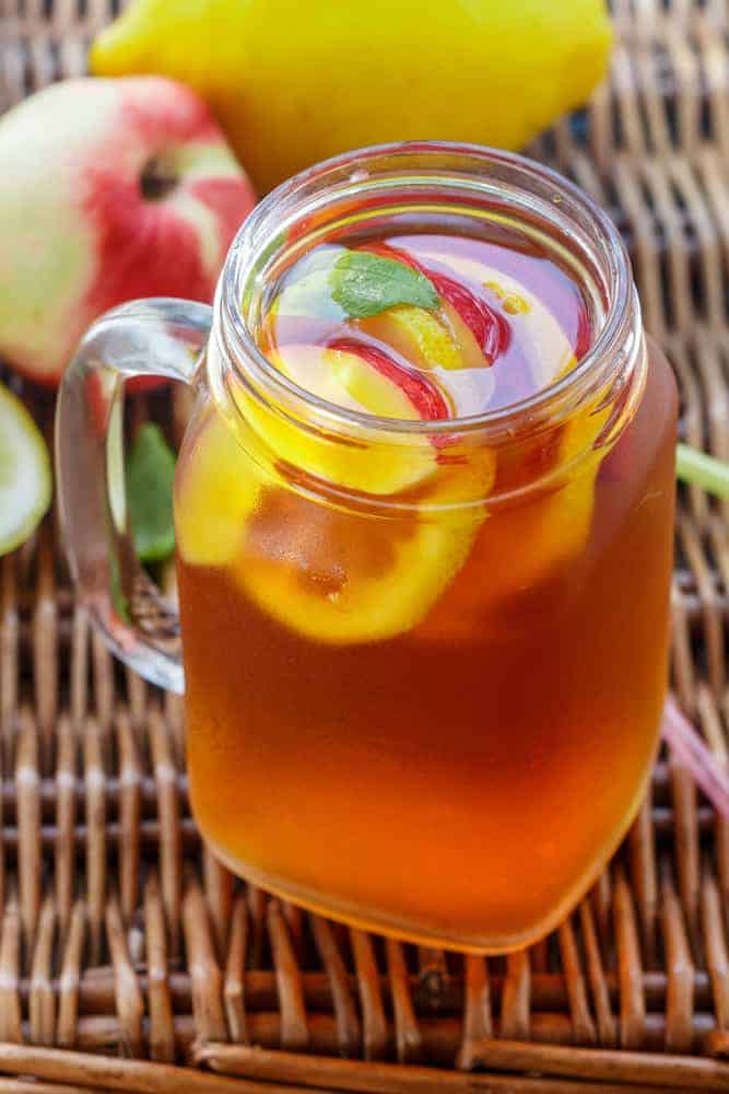 Peach Iced Tea in a mason jar glass with peach slices and mint on wicker table