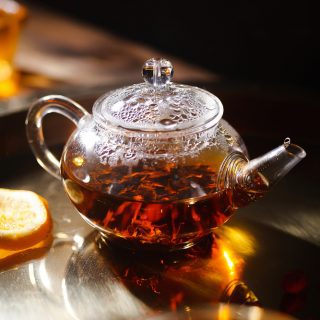 Small glass teapot brewing tea