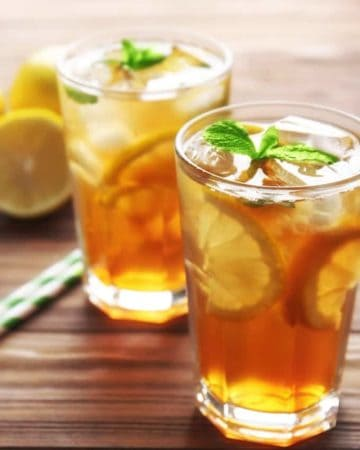 Glasses of iced tea with lemon slices and mint on wooden background
