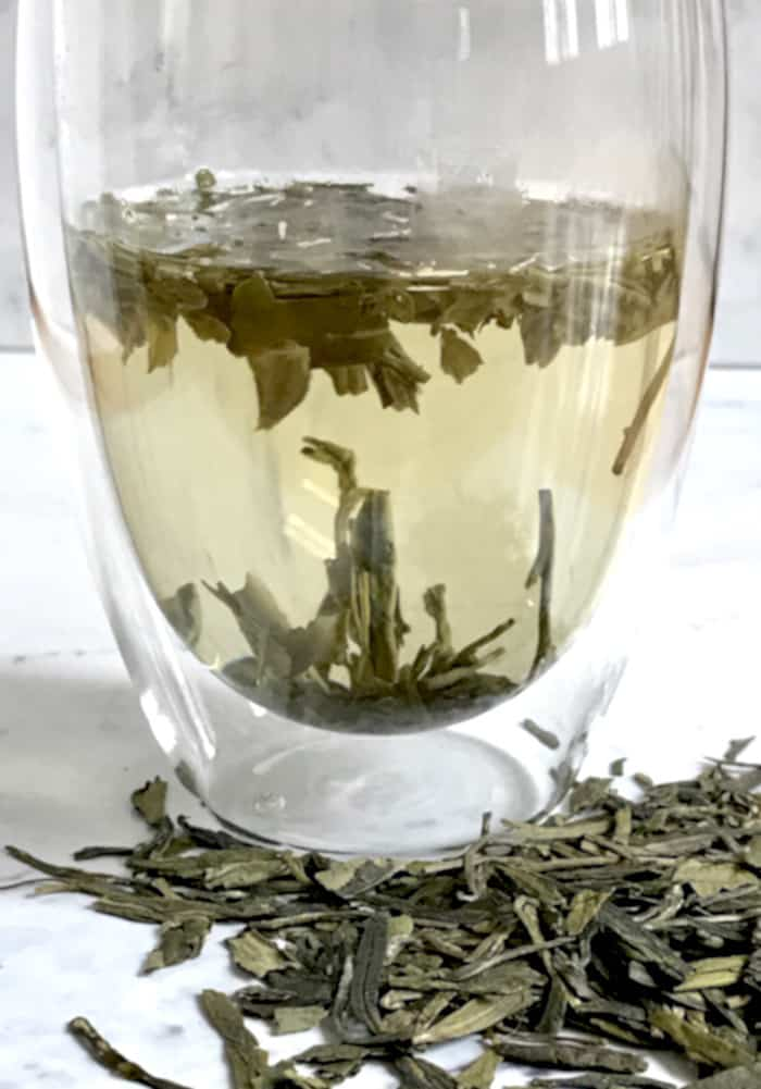 dragon well tea leaves brewing in glass