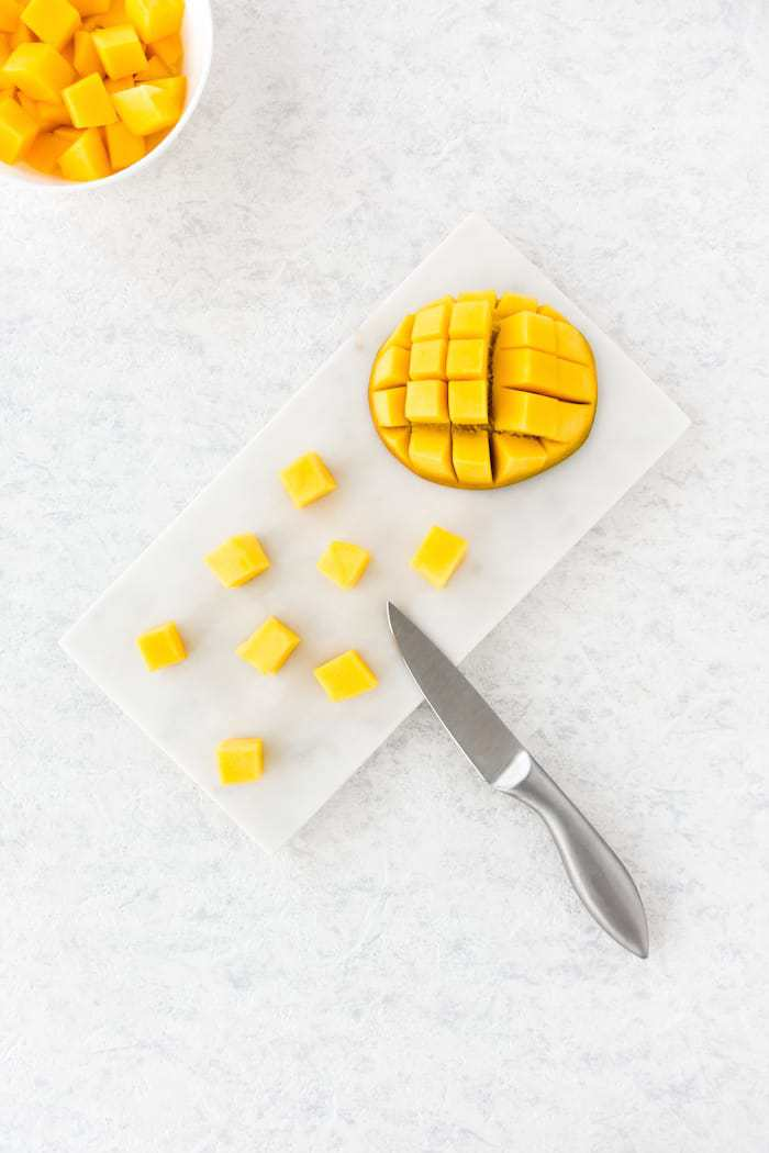 Mango cubes and cut mango half on white marble chopping board and in a white bowl. Top view. for mango chai smoothie