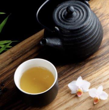 green tea in cups with black tea pot