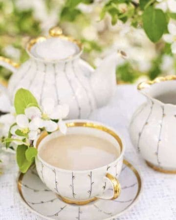 milk tea in teacup with teapot and flowers