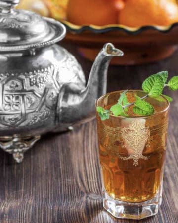 Morrocan mint tea in Turkish tea glass with tea pot in background