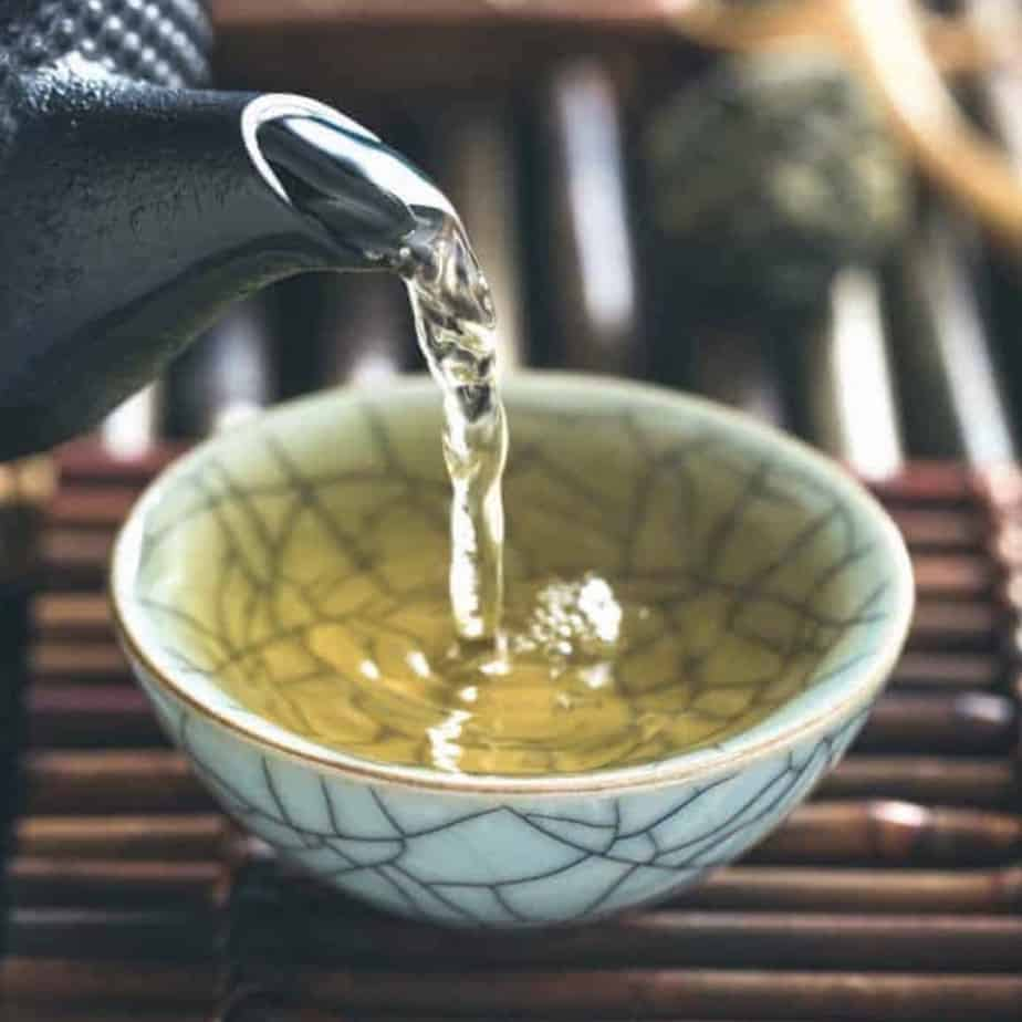 pouring green tea into tea bowl