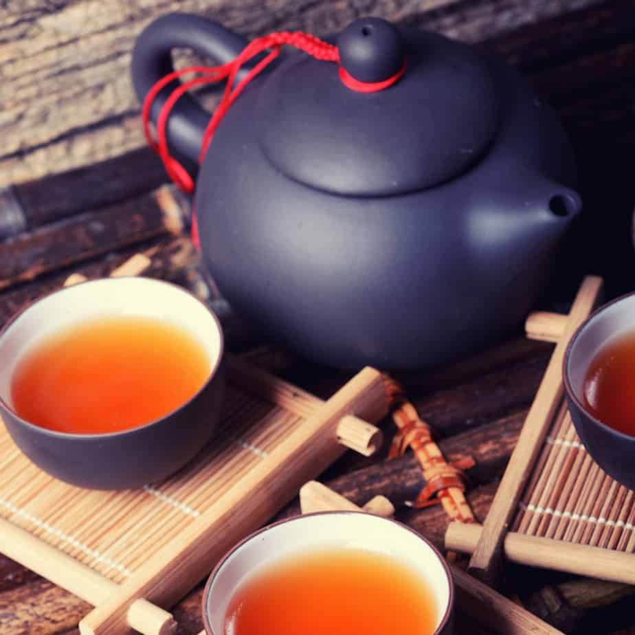 Chinese black tea in cups on bamboo with teapot
