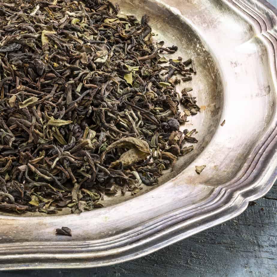darjeeling tea dried leaves on silver plate