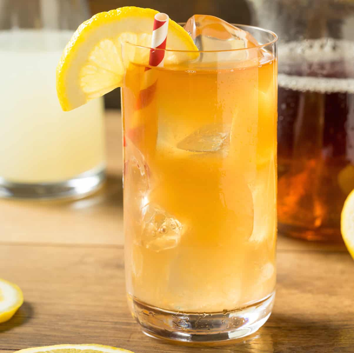 arnold palmer drink in glass with straw and lemon slice