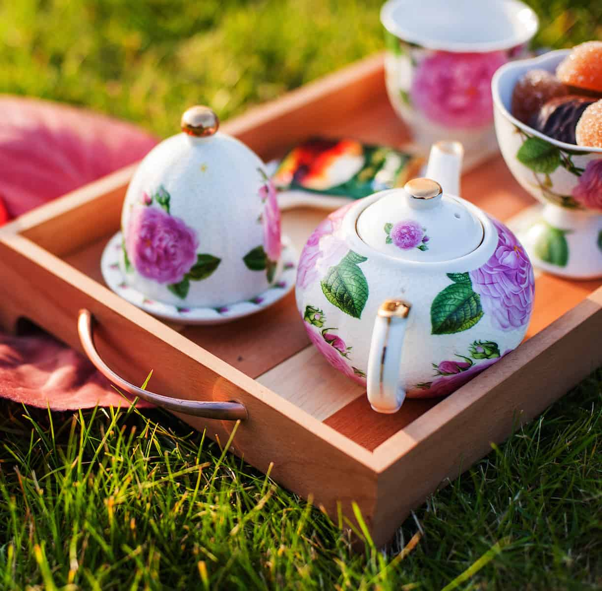 tea outside. teapot and tea cups in wooden tray outdoors