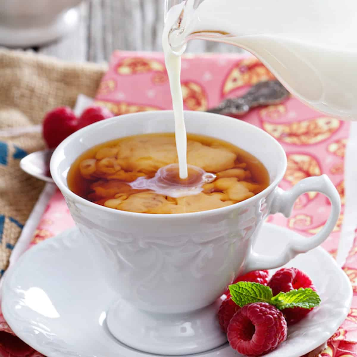 pouring milk into a white cup with with black tea sitting in a saucer and berries